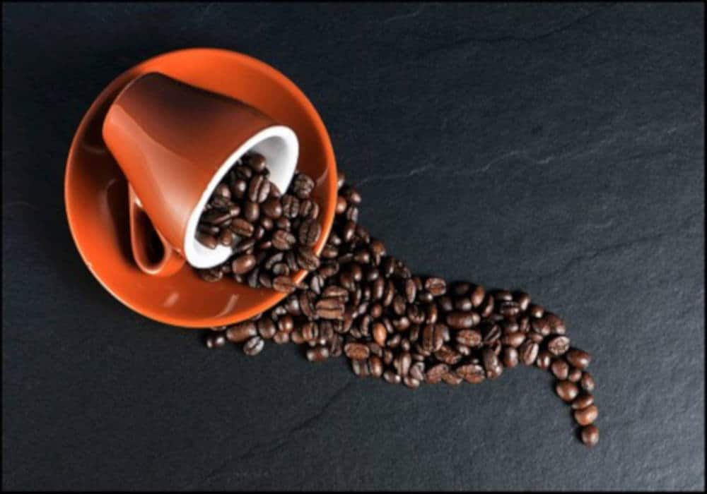 Roasted coffee beans in an orange mug by The Healthy RD