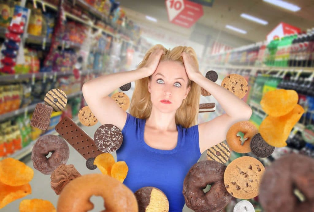 Woman showing fear with donuts and junk food by The Healthy RD