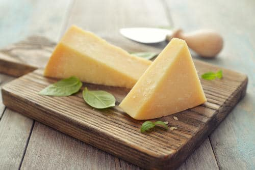 Aged parmesan cheese wedges on a wooden cutting board by The Healthy RD