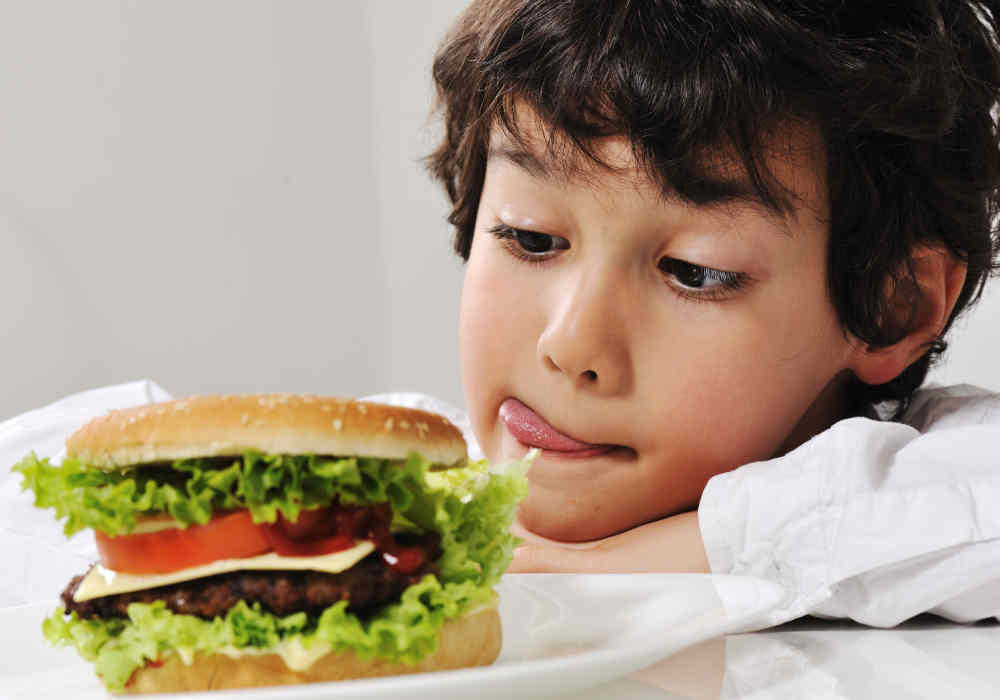 Boy tempted by a big burger by The Healthy RD