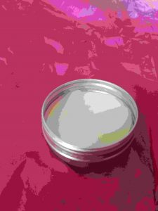 Salve in a tin with a pink tissue background by The Healthy RD