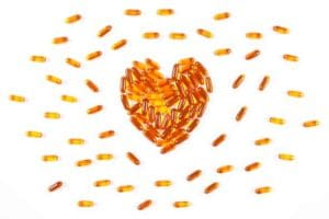 Heart shaped orange medical pills, capsules, or supplements by The Healthy RD