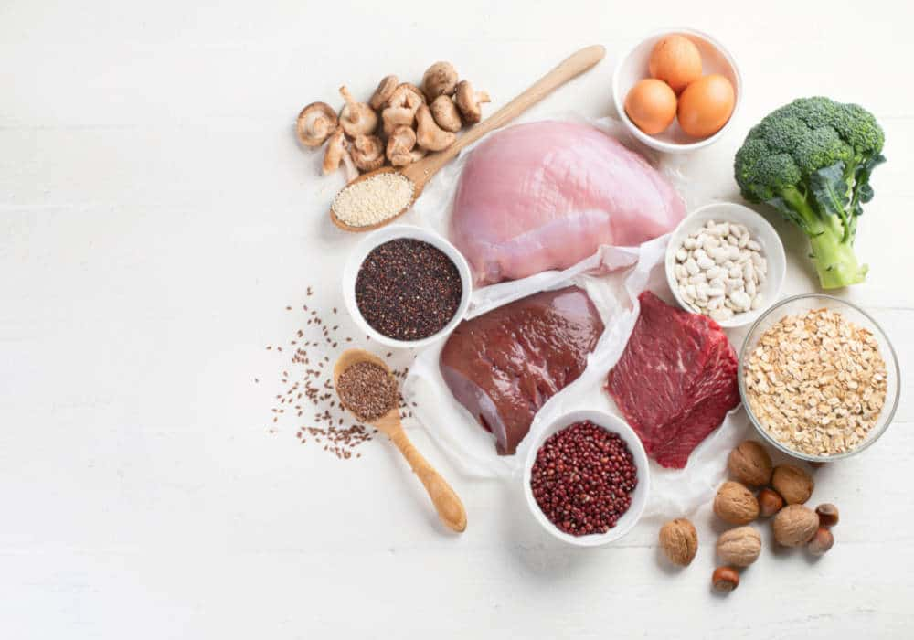 Chicken, liver, beans, eggs, broccoli, and seeds on a white background by The Healthy RD