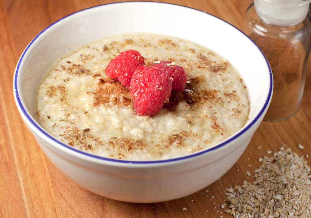 Bowl of low carb oatmeal with fresh raspberries and cinnamon by The Healthy RD
