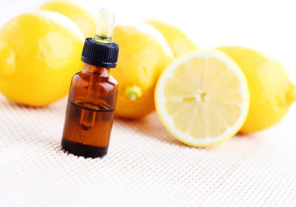 Fresh lemons and lemon essential oil on a white background by The Healthy RD