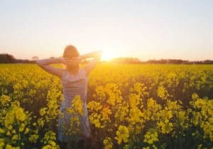 Woman in a field of tall yellow flowers enjoying the sunset by The Healthy RD