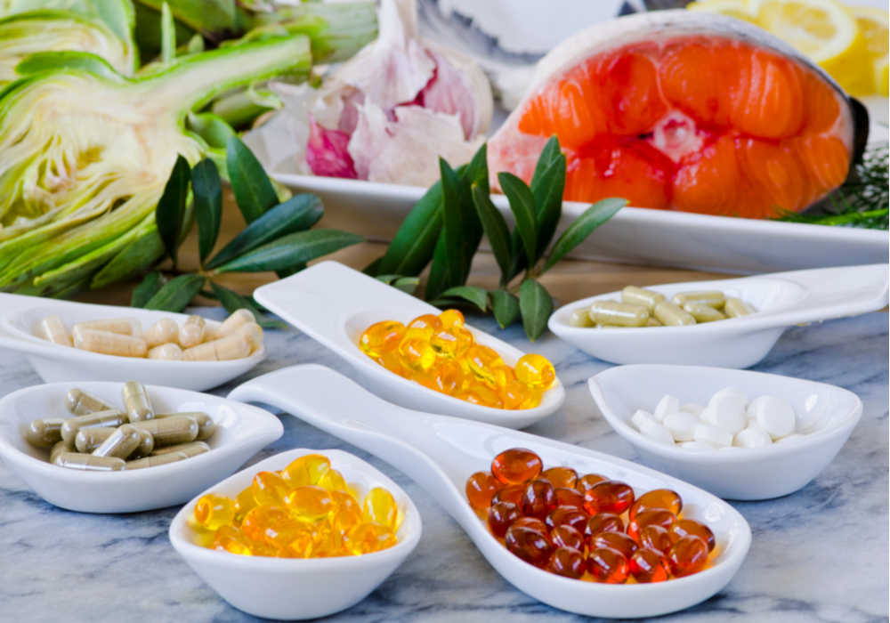 Supplement gelcaps assorted in white serving spoons and fresh vegetables and fish in the background by The Healthy RD