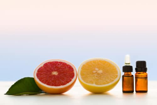 Fresh grapefruit and amber grapefruit essential oil bottles by The Healthy RD