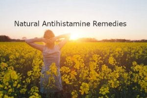 Woman in a field of yellow flowers and writing Natural Antihistamine Remedies by The Healthy RD