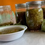Canning salsa verde with jars, a bowl of fresh tomatillo salsa, onions, poblano peppers, and tomatillos by The Healthy RD