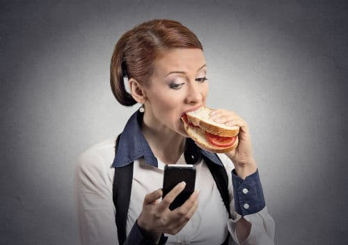 Woman with red hair eating a white bread sandwich while reading nutrition news on her phone by The Healthy RD