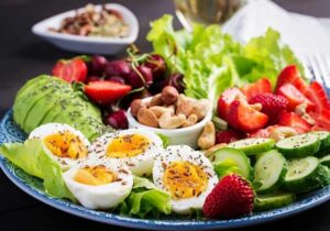 Mitochondria diet plate with hard boiled eggs, green vegetables, strawberries, and nut by The Healthy RD