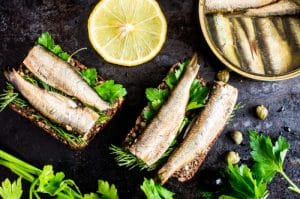 Best sardines in a can depicted on a sandwich with fresh lemon slices by The Healthy RD