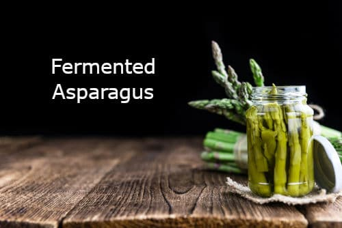 Fermented asparagus and fresh asparagus on a wood cutting board by the Healthy RD
