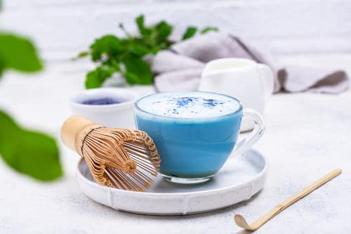 Blue spirulina latte on a white background in a clear mug by The Healthy RD