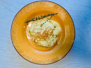 Low carb protein pancakes on an orange plate with sprig of thyme by The Healthy RD