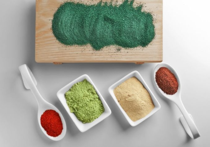 Green superfood powder, red superfood powders in serving dishes and spoons depicting the best superfood powders by The Healthy RD