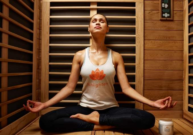 Sauna stress relief depicting a young woman meditating in a Sunlighten sauna by The HealthyRD