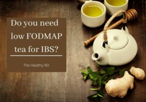 White tea pot and cups on a brown background with fresh ginger and mint leaves with wording do you need low FODMAP tea for IBS by The Healthy RD
