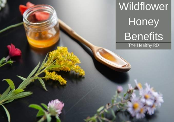 A jar and wooden spoonful of wildflower honey with fresh wildflowers on a slate colored background with wording wildflower honey benefits by The Healthy RD