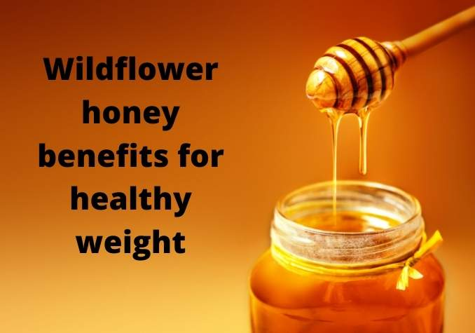 Image of wildflower honey and honey dipper stick with dripping honey on a golden background with wording wildflower honey benefits for healthy weight by The Healthy RD