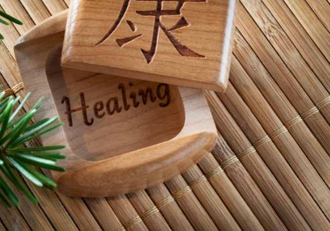 A bamboo mat with a wooden box with the writing healing inside with pine bough by The Healthy RD