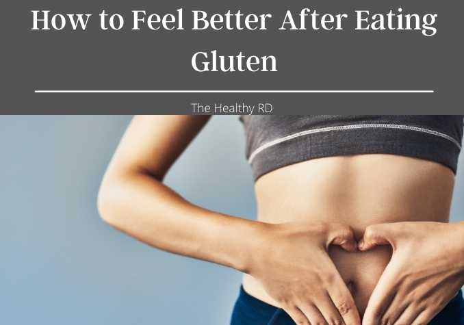 Woman holding her hands in a heart shape over her belly button in a dark gray top with wording how to feel better after eating gluten by The Healthy RD