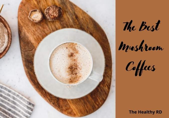 Fancy coffee with foam in a white mug on a wooden cutting board with mushrooms on a white background with wording the best mushroom coffee by The Healthy RD